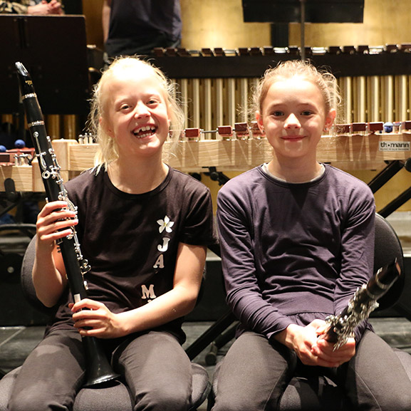 Two girls holding instruments